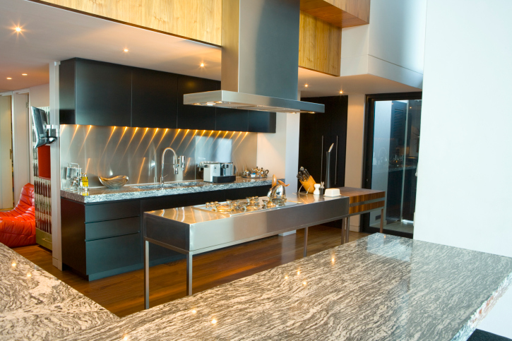 Modern kitchen with stainless steel island, black cabinets, hard wood floor and granite countertops