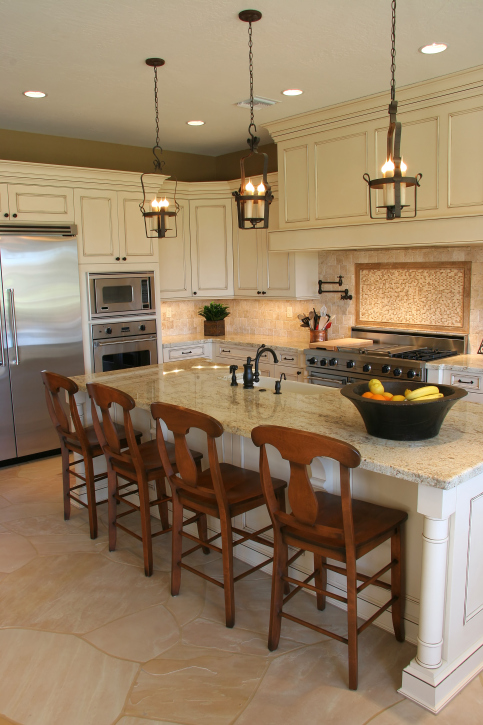 Ornate white kitchen with stainless steel appliances and drop-down lighting