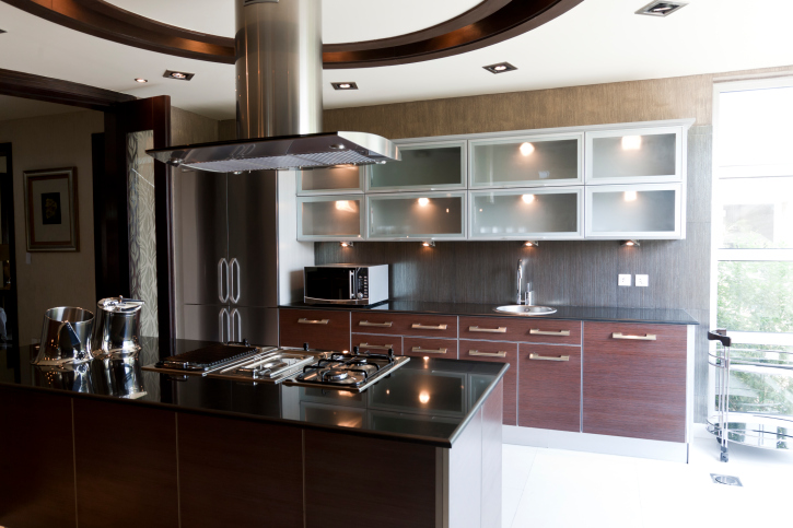 Sleek modern kitchen with wood and silver cabinets, black island and white floor