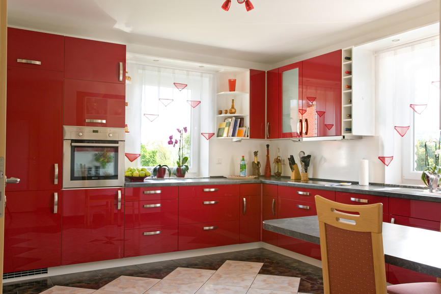 Simple all-red modern kitchen with small dine-in table and chairs
