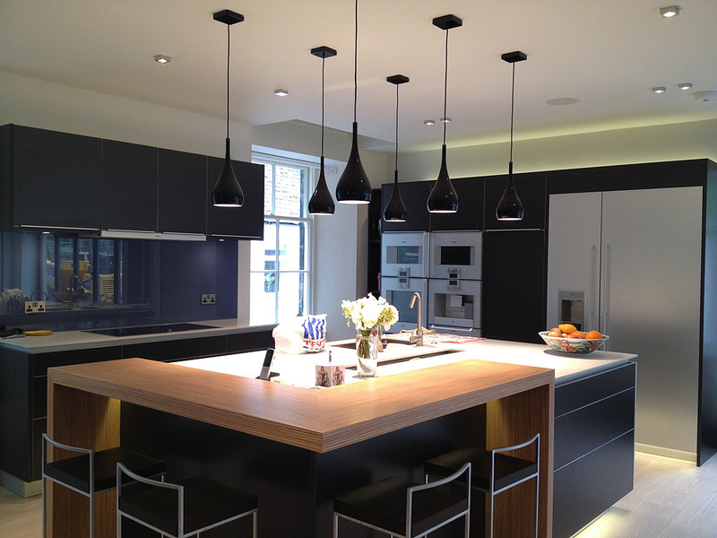 Image Of Dark Kitchen With Large Square Island And Stainless Steel