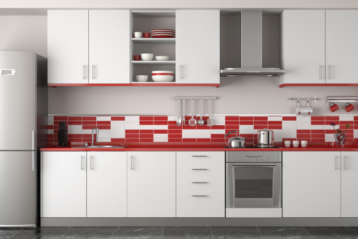 Minimalist white kitchen with red back splash accompanied with stainless steel appliances
