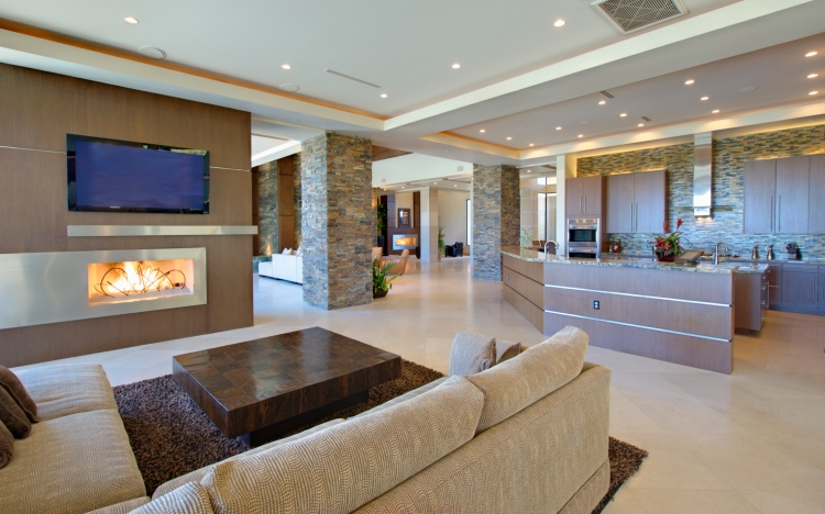 Living room with small sectional sofa, gas fireplace, recessed pot lighting and flat screen TV