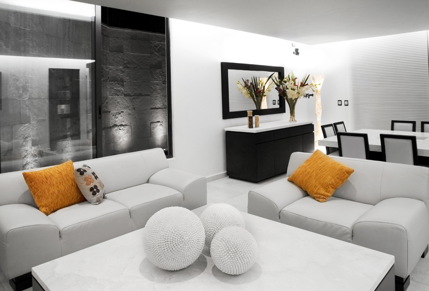 Small white living room with crisp white furniture accented with orange  pillows and square white coffee. 78 Stylish Modern Living Room Designs in Pictures You Have to See