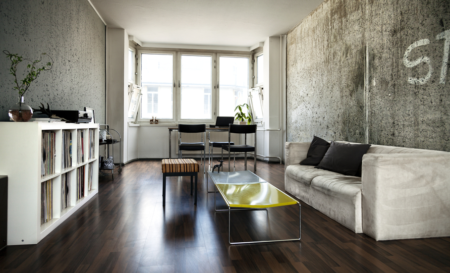 Beautiful Living Room With Concrete Walls, Dark Hard Wood Floor, White Sofa  And White