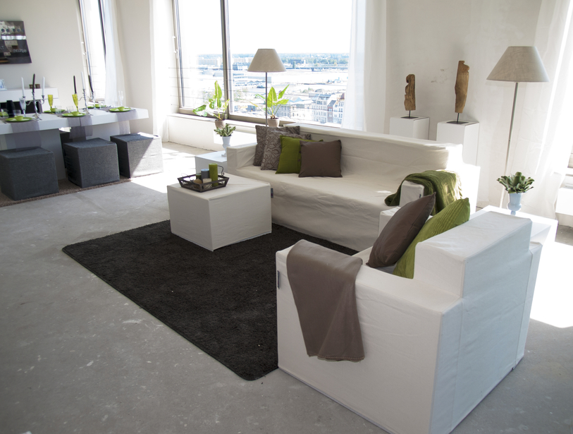 Simple living room with large white sofa and reading chair with white cube coffee table