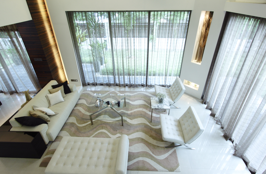 Cream color scheme living room with modern chairs, rug and floor-to-ceiling windows