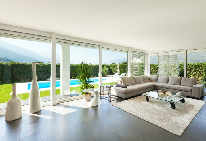 Modern Living Room Overlooking Pool With Sectional Couch And A Wall Of  Windows
