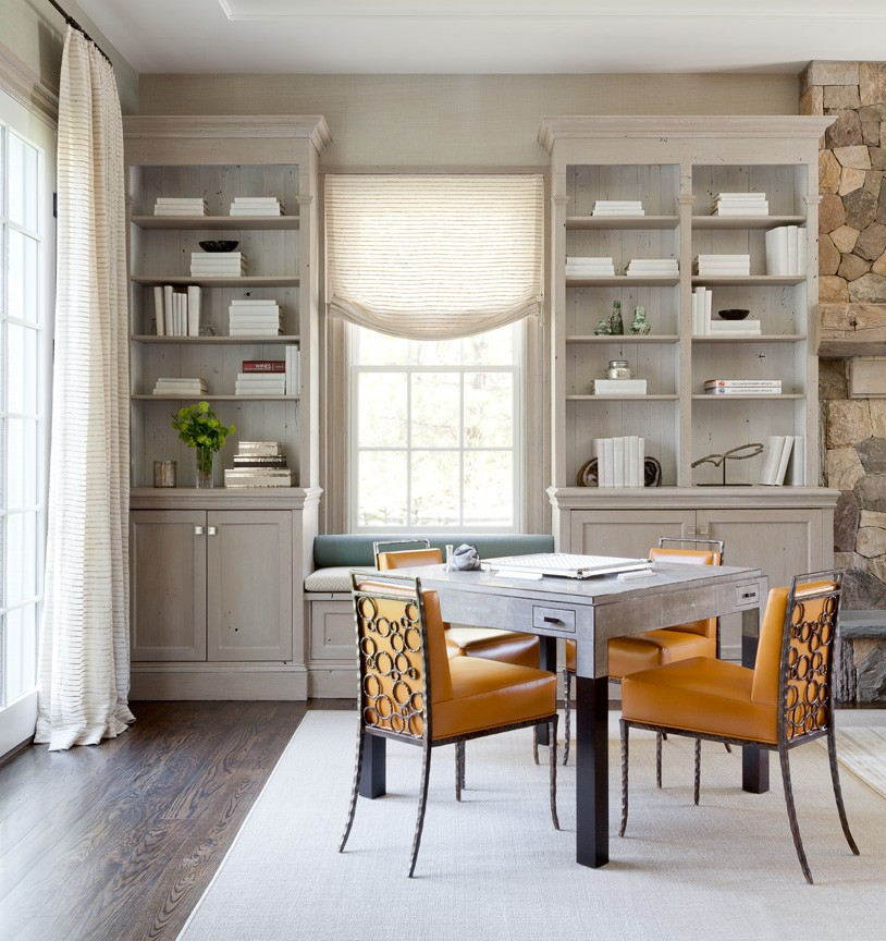Dining table with orange chairs on white rug. Room has floor-to-ceiling built-in bookshelves framing a window.