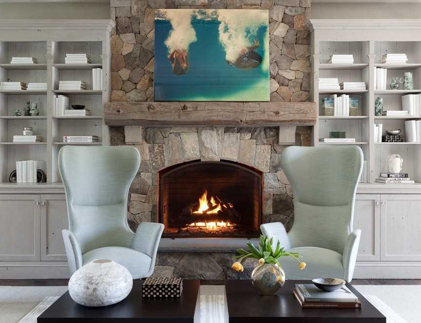 Two modern reading chairs next to fireplace. Fireplace is framed with floor-to-ceiling built-in bookshelves in grey color scheme