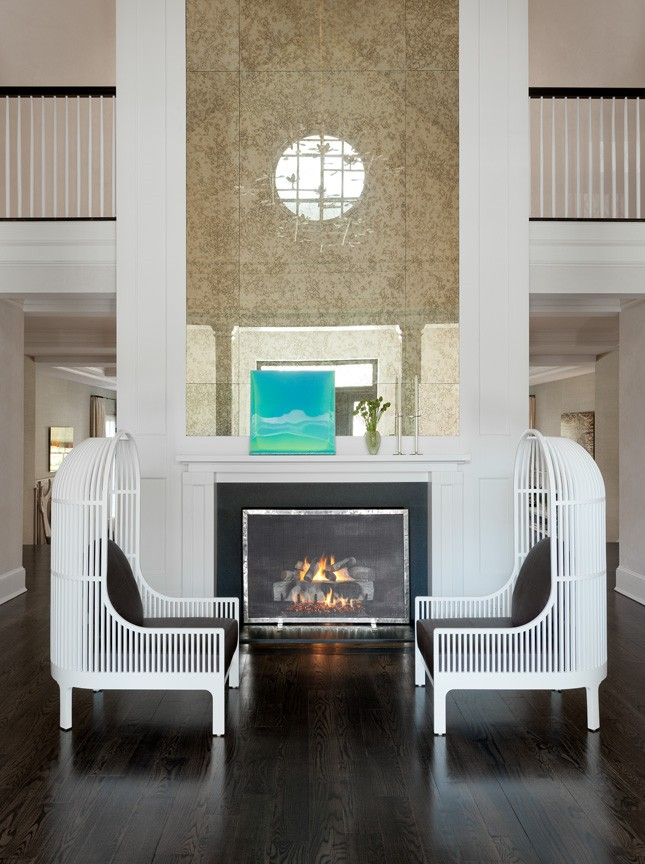 Reading area with dark wood floor, custom designed white reading chairs and fireplace with white mantle