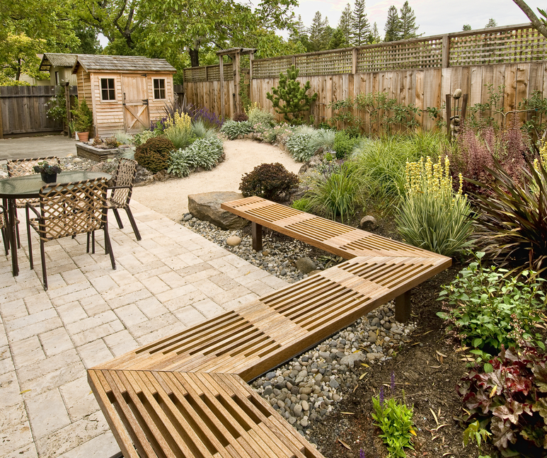 backyard with large pinwheel pattern patio bordered with built in wooden bench - Outdoor Patio Design Ideas