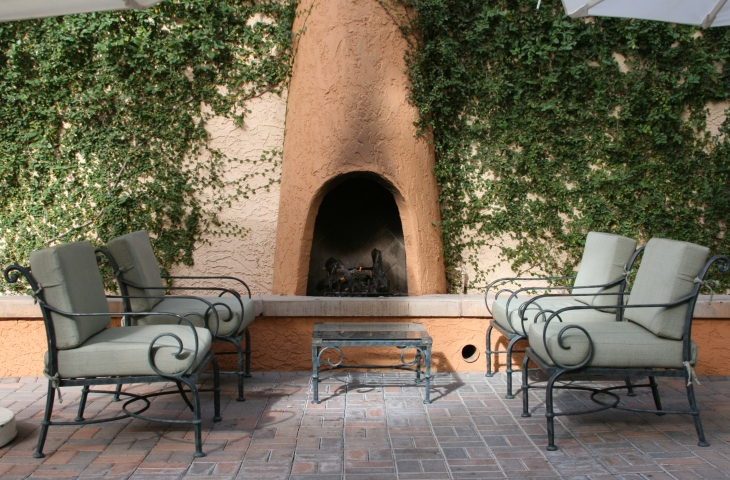 Built-in adobe patio fireplace on edge of brick patio