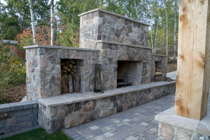 Large custom brick fireplace on edge of backyard patio