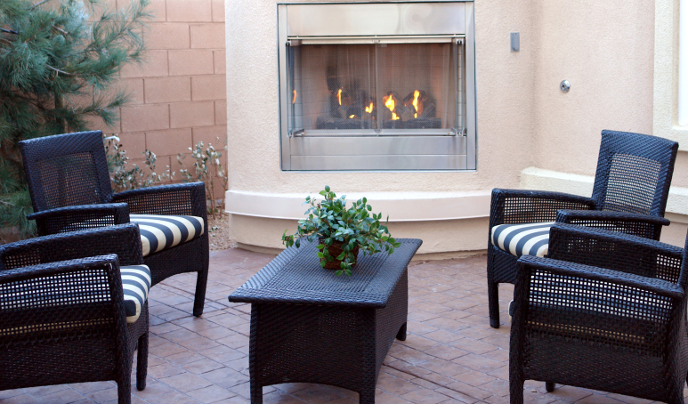 Brick patio with stylish patio chairs seated around patio fireplace