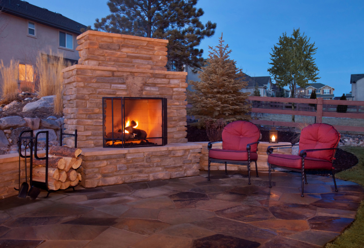 Elegant brick wood-burning fireplace on edge of large flatgstone patio