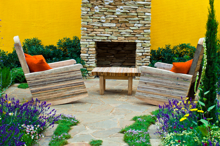 Brick fireplace on small flagstone patio against yellow wall