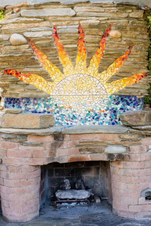 Brick fireplace with mosaic of the sun