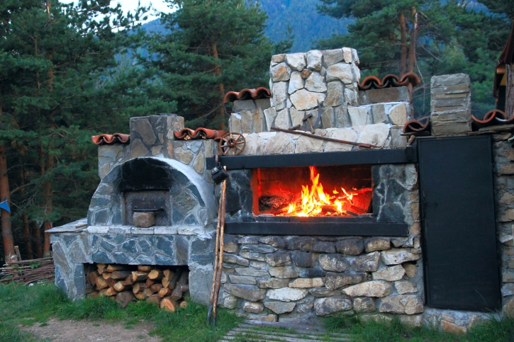 Large rock fireplace with wood storage section