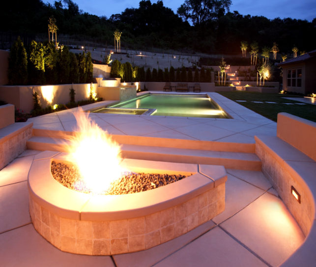 Built-in fire pit on patio wrapping around swimming pool