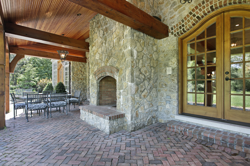 Covered brick patio with stone fireplace built into home's exterior wall