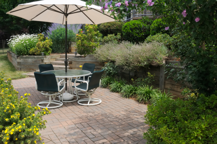 Brick patio in the the middle of the yard with umbrella surrounded by lush gardens