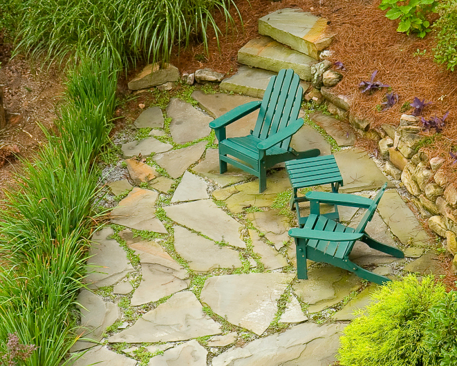 Flagstone patio with tall grass border and also bordered by sloping garden