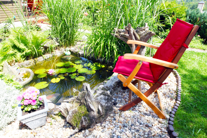 Gravel patio with lily pond and tall grasses