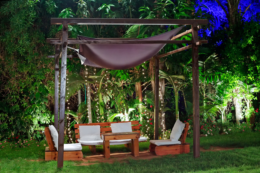 Large gazebo in the garden with plush modern patio furniture