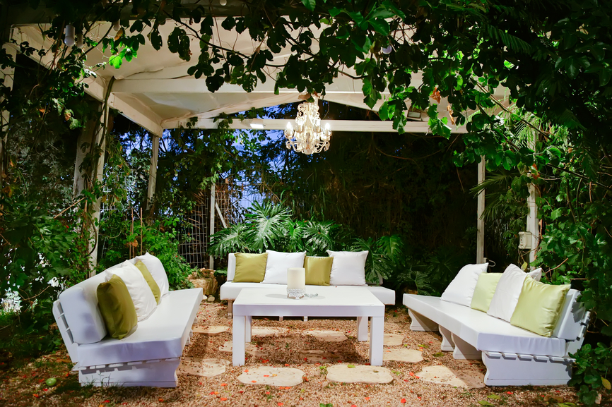 Large garden gazebo with white patio furniture surrounded by tropical plants and trees