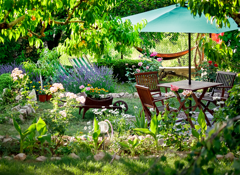 Fun patio in the middle of gardens with small patio table and umbrella. Hammock off to the side.