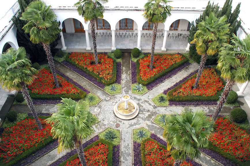 Elaborate courtyard patio containing a series of gardens containing flowers and trees. Fountain in the middle.