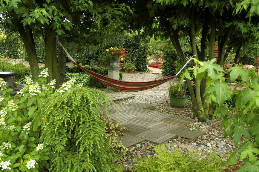 Stylish brick and rock patio among plants and trees with hammock