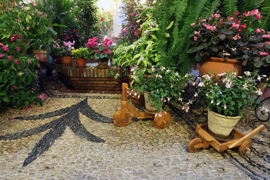 Small Stone Patio Loaded With Potted Plants And Flowers
