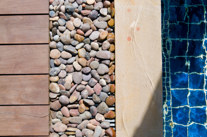 Picture of wood deck edged with narrow pebble garden and light wood around the pool