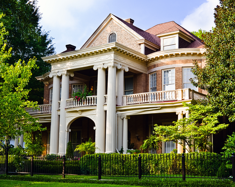 Historic brick southern mansion incorporating several architectural styles most notably Greek Revival elements with the imposing 4 pillars and symmetrical design combined with elements of Georgian architecture