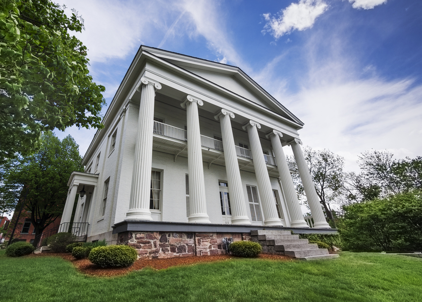Greek Revival mansion in white where columns span only the front of the home