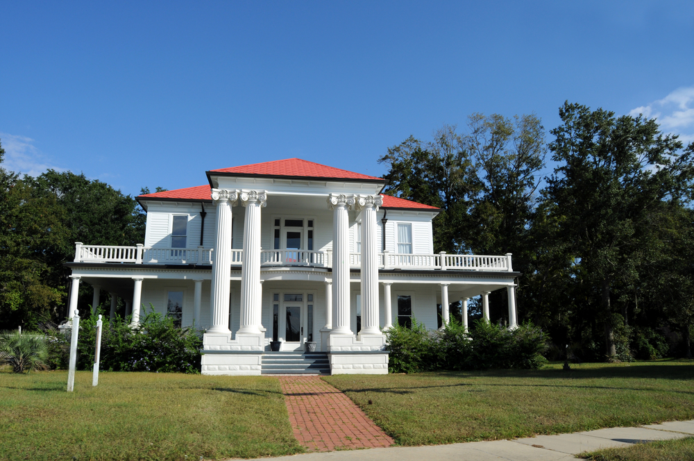 White mansion with red roof incorporating antebellum architectural features including 4 large pillars and wrap-around verandas on the first and second floors