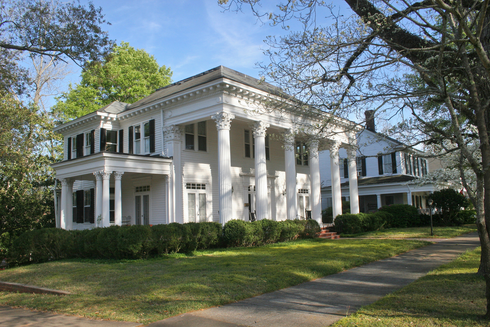 Greek revival plantation home. This home is a stereotypical Antebellum mansion with large pillars along the front facade on a large estate.