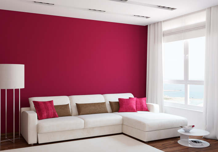 Minimalist living room with deep red wall and sofa pillows with white sofa, white drapes and white rug.