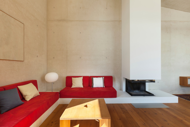 Living with concrete walls, white fireplace and red sofas.