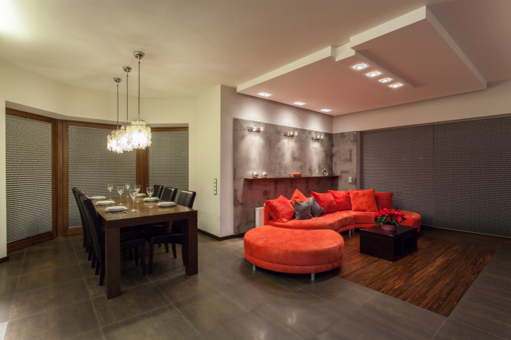 Open concept dining and living room with semi-circular red sofa.