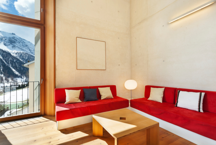Living room with hard wood floor, concrete walls and floor-to-ceiling window highlighted with red sofas.