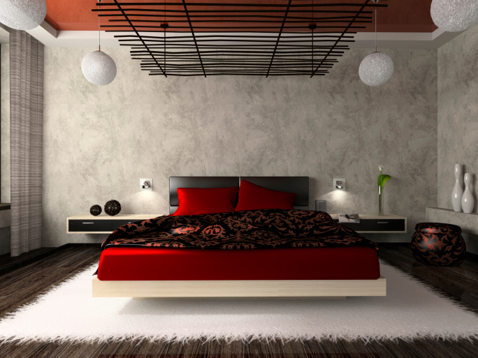 Dark bedroom with dark wood floor, white rug and red bed.