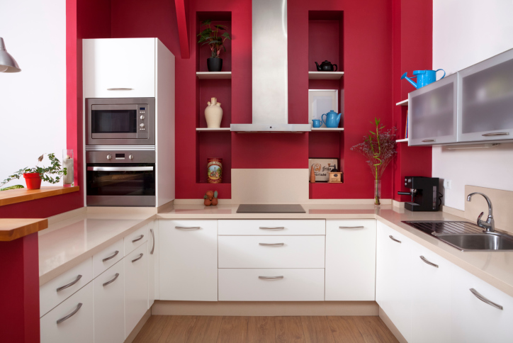 Kitchen with red and white cabinets and natural-wood floor.