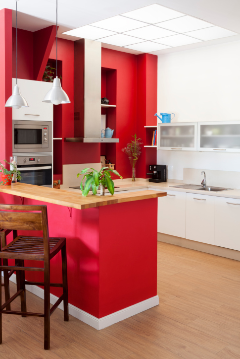 Kitchen with red peninsula and shelving with white cabinets and wood flooring.