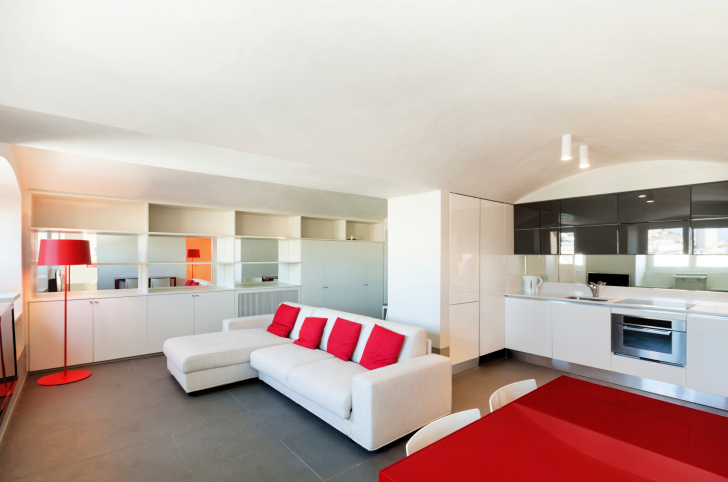 Apartment with red-accented living room and red dining table.
