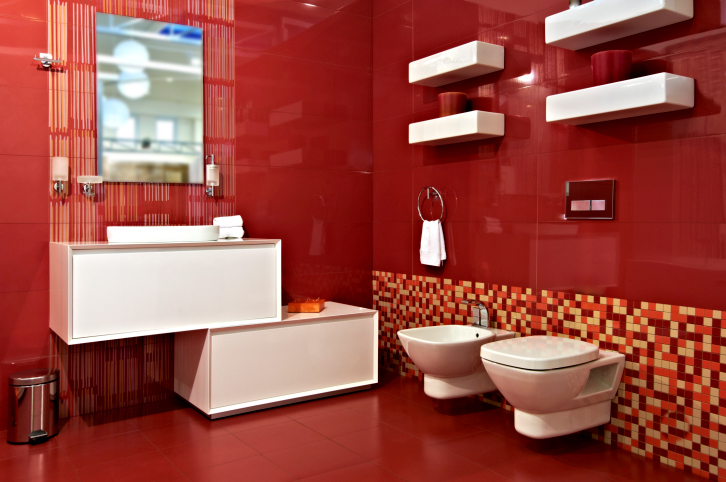 Deep red bathroom with red walls and floor and white vanity, toilet and shelves
