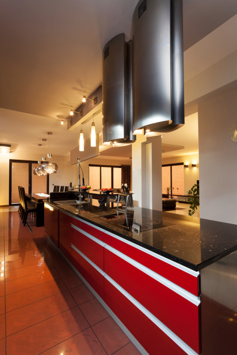 Modern kitchen with red peninsula and black counter tops