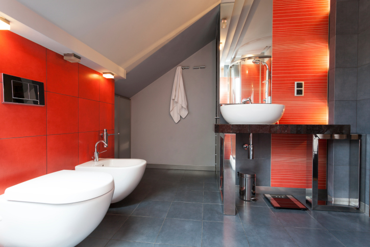 Grey and red bathroom with white toilet and white vessel basin.